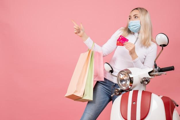 Vue de face jeune femme tenant des sacs à provisions et des cartes de crédit près de cyclomoteur