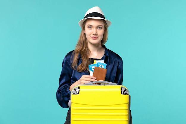 Vue de face jeune femme tenant ses billets et se préparant pour le voyage sur le fond bleu voyage avion mer vacances voyage voyage