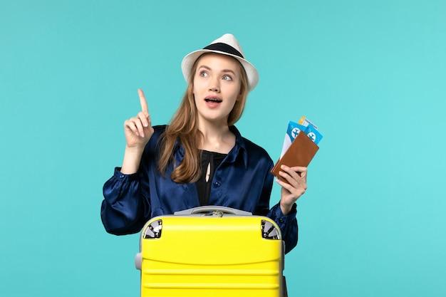 Vue de face jeune femme tenant ses billets et se préparant pour le voyage sur le fond bleu voyage voyage avion mer vacances voyage