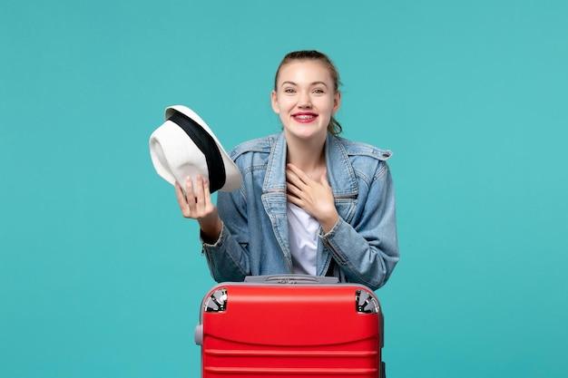 Vue de face jeune femme tenant son chapeau et se prépare pour le voyage en riant sur l'espace bleu