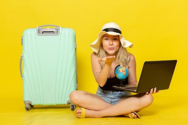 Vue de face jeune femme tenant son ordinateur portable et envoi de baisers aériens