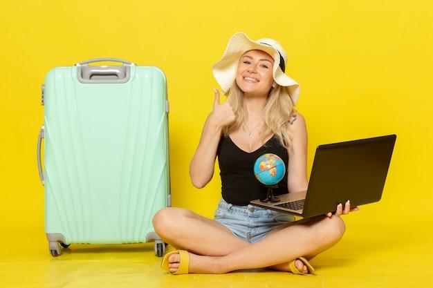 Vue de face jeune femme tenant son ordinateur portable et globe