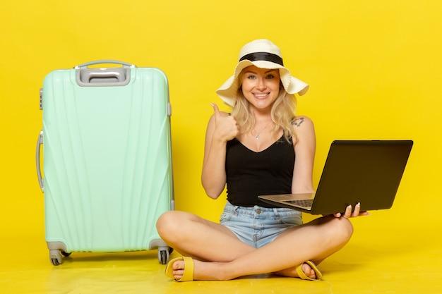 Vue de face jeune femme tenant son ordinateur portable et souriant