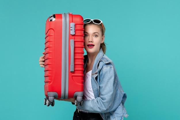 Vue de face jeune femme tenant son sac rouge et préparation pour le voyage sur le plancher bleu voyage vacances voyage voyage mer