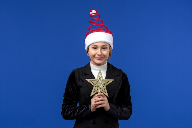 Vue de face jeune femme tenant star toy sur fond bleu couleur nouvel an femme vacances
