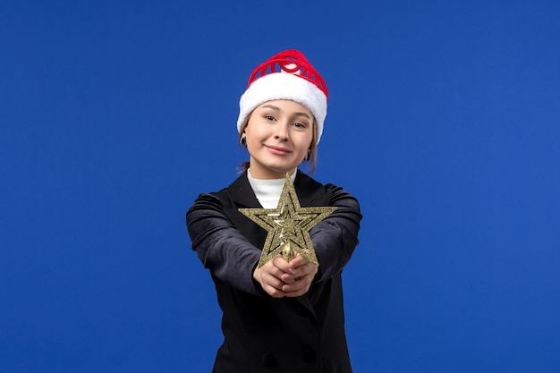 Vue de face jeune femme tenant star toy sur fond bleu couleur vacances femme nouvel an