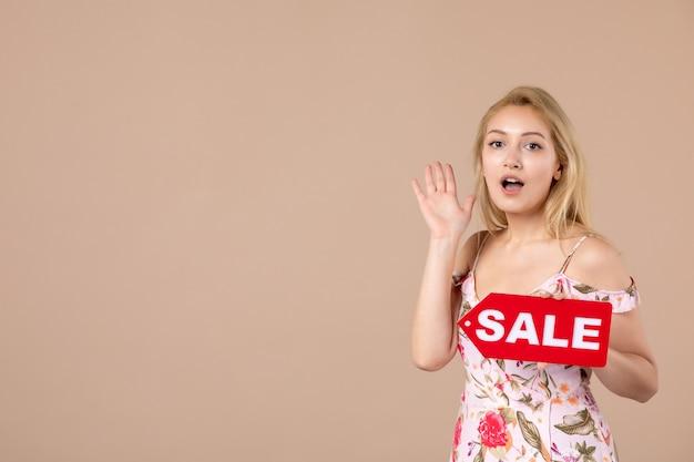 Vue de face d'une jeune femme tenant un tableau de vente rouge sur un mur marron