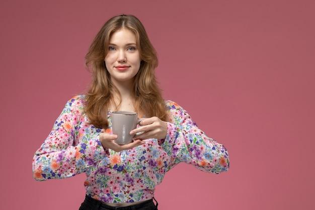 Vue de face jeune femme tenant la tasse dans sa main