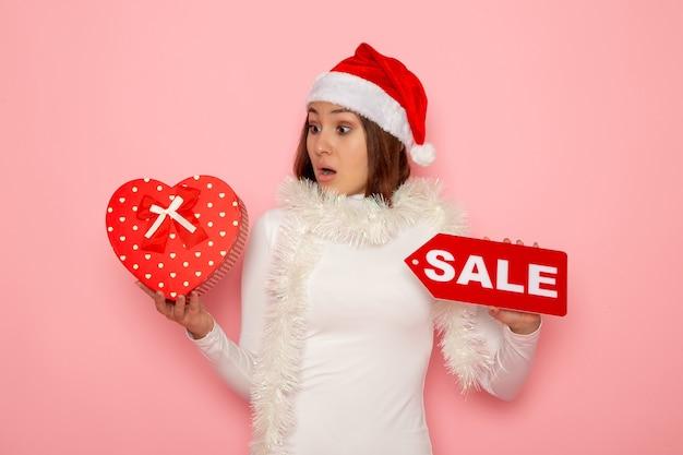 Vue de face jeune femme tenant vente écrit et présent sur le mur rose couleurs mode vacances nouvel an neige noël