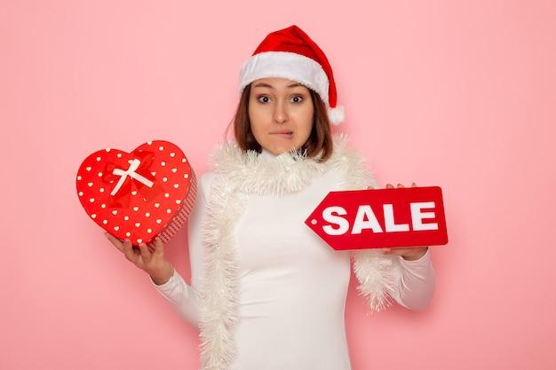 Vue de face jeune femme tenant vente écrit et présent sur le mur rose neige noël couleur vacances nouvel an mode
