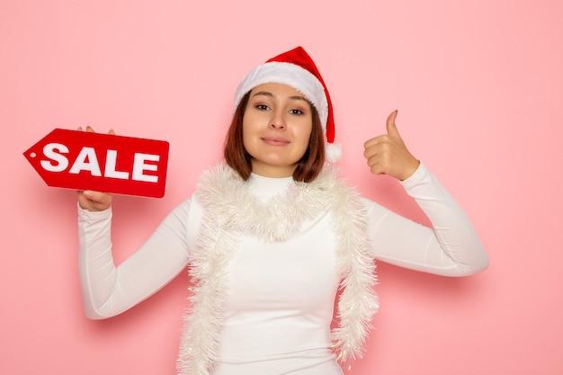 Vue de face jeune femme tenant vente figure écrite sur les couleurs du mur rose vacances nouvel an mode neige noël
