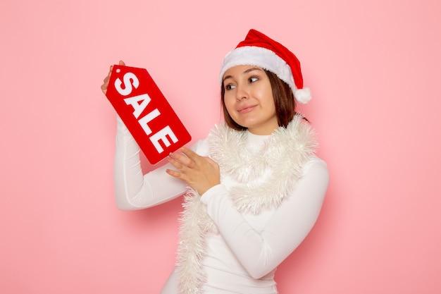 Vue de face jeune femme tenant vente figure écrite sur le mur rose couleur émotion neige noël nouvel an vacances