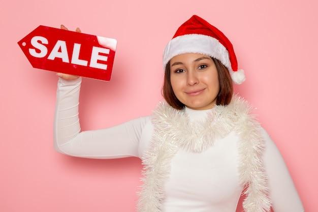 Vue de face jeune femme tenant vente figure écrite sur le mur rose couleur neige noël nouvel an mode vacances