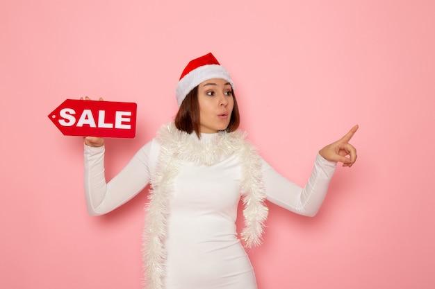 Vue de face jeune femme tenant vente figure écrite sur le mur rose couleur noël nouvel an vacances mode neige
