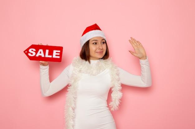 Vue de face jeune femme tenant vente figure écrite sur le mur rose couleur noël nouvel an vacances neige