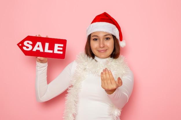 Vue de face jeune femme tenant vente figure écrite sur le mur rose couleur nouvelle année vacances mode neige