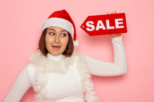 Vue de face jeune femme tenant vente figure écrite sur le mur rose couleur vacances nouvel an mode neige noël