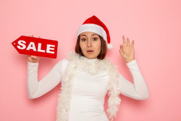 Vue de face jeune femme tenant vente figure écrite sur le mur rose couleur vacances nouvel an neige noël