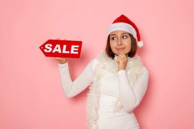 Vue de face jeune femme tenant vente figure écrite sur mur rose vacances noël nouvel an couleur neige