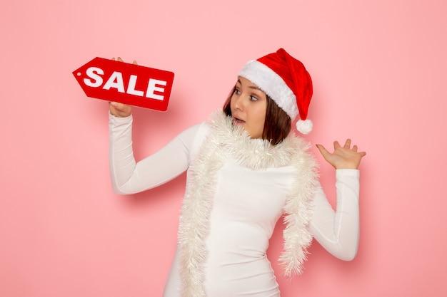 Vue de face jeune femme tenant vente figure écrite sur mur rose vacances noël nouvel an mode couleur neige