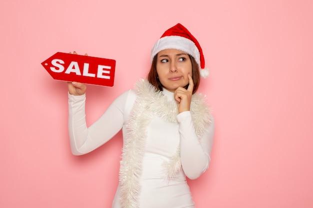Vue de face jeune femme tenant vente figure écrite pensée sur mur rose vacances noël nouvel an mode couleur neige