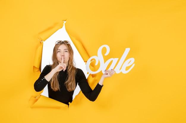 Vue de face jeune femme tenant une vente par écrit à travers un trou de papier déchiré dans le mur