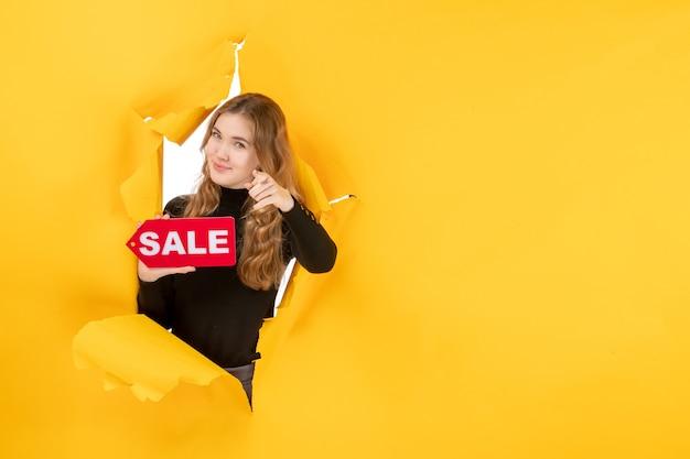 Vue de face jeune femme tenant une vente rouge écrit sur un mur jaune
