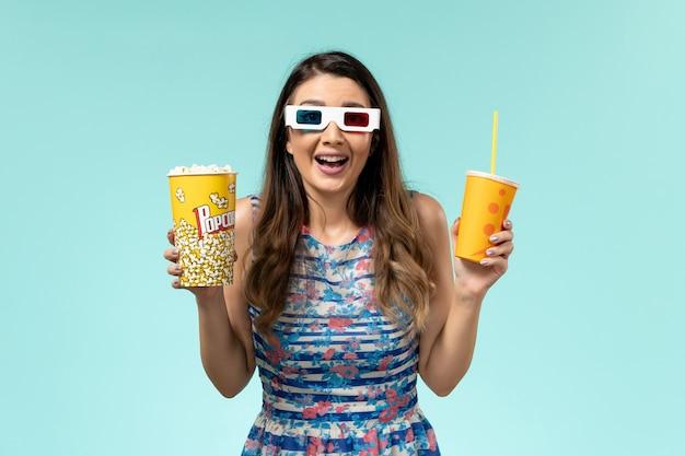 Vue de face jeune femme tenant un verre de maïs soufflé dans des lunettes de soleil sur une surface bleu clair