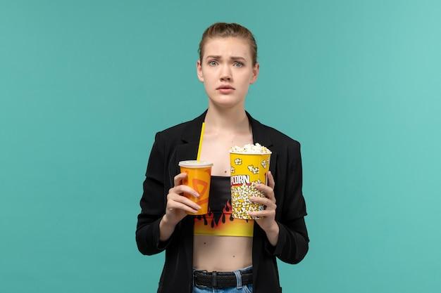 Vue de face jeune femme tenant un verre de maïs soufflé et regarder un film sur la surface bleu clair