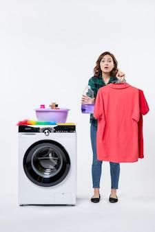 Vue de face d'une jeune femme tenant des vêtements propres et de la poudre liquide de la machine à laver sur un mur blanc