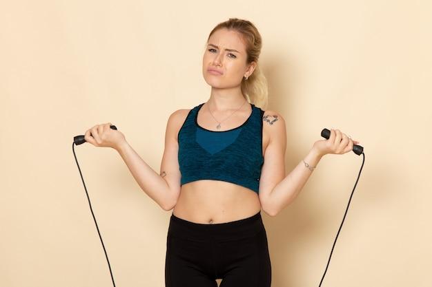 Vue de face jeune femme en tenue de sport, faire des exercices avec des cordes à sauter