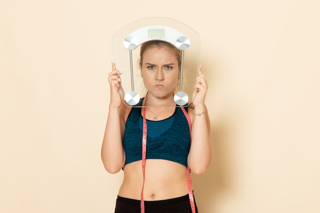 Vue de face jeune femme en tenue de sport tenant des échelles sur un bureau blanc fit sport beauté exercice de santé du corps