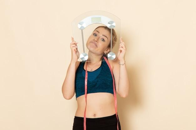 Vue de face jeune femme en tenue de sport tenant des échelles sur un mur blanc fit sport beauté exercices de santé du corps