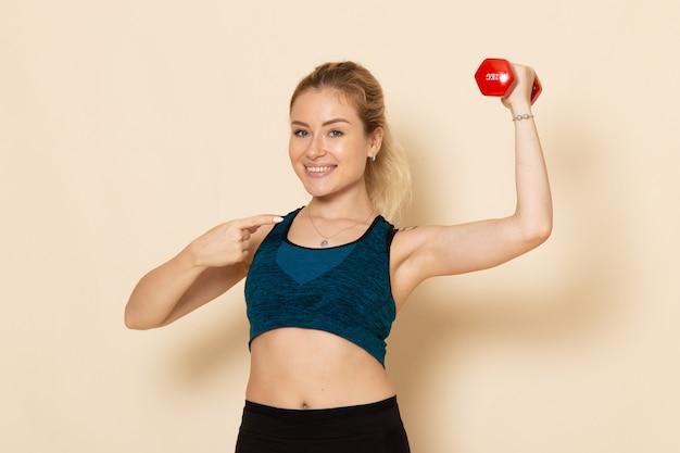 Vue de face jeune femme en tenue de sport tenant des haltères sur le mur blanc sport corps santé beauté séance d'entraînement femme