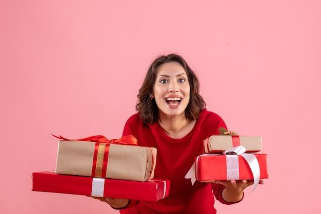 Vue de face jeune femme transportant des cadeaux de noël sur le rose
