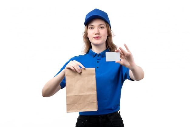 Une vue de face jeune femme travailleur de messagerie de service de livraison de nourriture souriant tenant le paquet de livraison de nourriture et carte blanche sur blanc