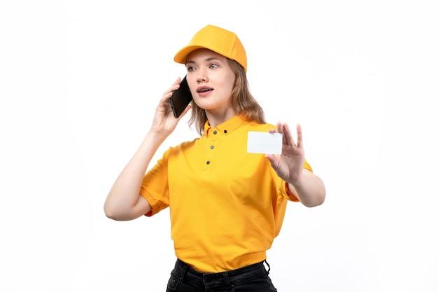 Une vue de face jeune femme travailleur de messagerie de service de livraison de nourriture tenant une carte blanche et parler au téléphone sur blanc