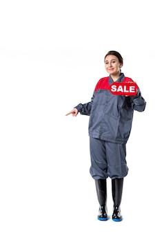 Vue de face jeune femme en uniforme tenant la plaque signalétique de vente sur fond blanc