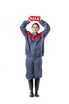 Vue de face jeune femme en uniforme tenant la plaque signalétique de vente rouge sur fond blanc