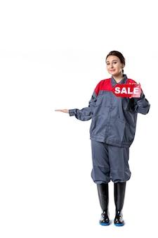 Vue de face jeune femme en uniforme tenant vente plaque signalétique écrite sur fond blanc