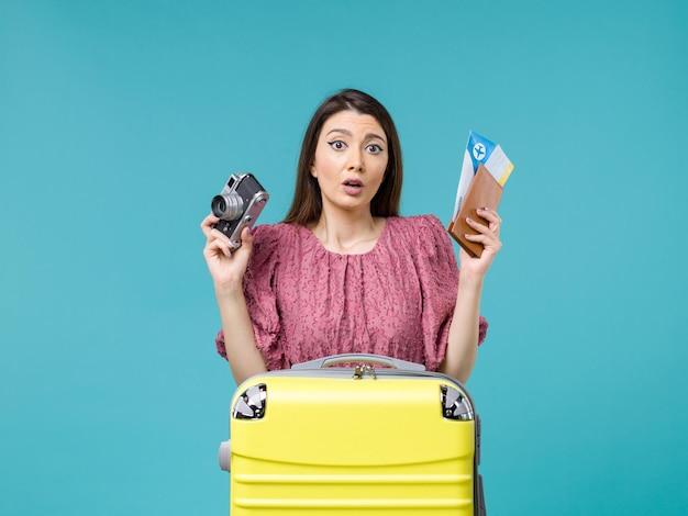Vue de face jeune femme va en vacances tenant la caméra et des billets sur fond bleu clair voyage vacances femme mer à l'étranger