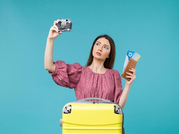 Vue de face jeune femme va en vacances tenant la caméra et les billets sur le plancher bleu voyage vacances femme mer à l'étranger