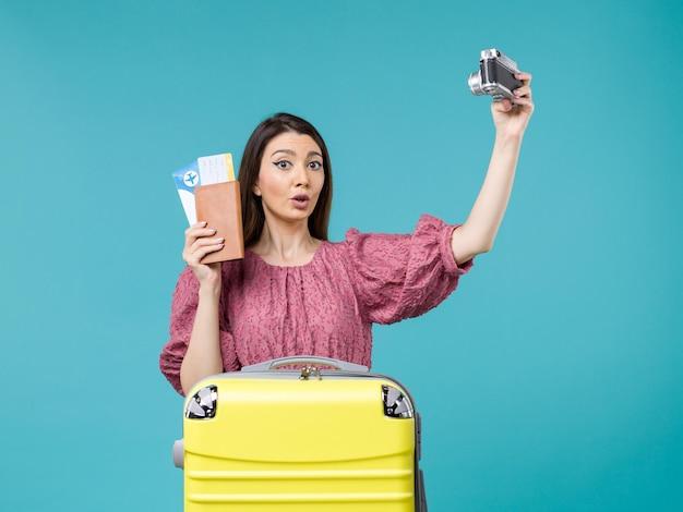 Vue de face jeune femme va en vacances tenant la caméra en prenant une photo sur un fond bleu voyage vacances femme à l'étranger mer