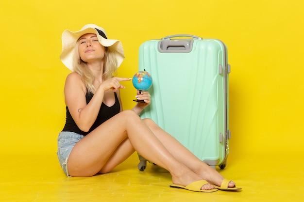 Vue de face jeune femme en vacances assis avec son sac vert holding globe sur mur jaune clair voyage féminin voyage soleil couleur mer