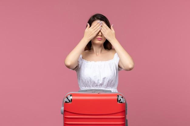 Vue de face jeune femme en vacances couvrant ici les yeux sur un fond rose à l'étranger voyage en mer voyage voyage voyage