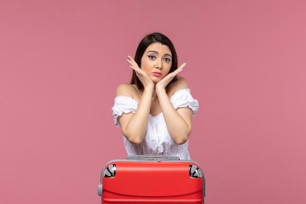 Vue de face jeune femme en vacances posant sur fond rose à l'étranger voyage en mer voyage voyage voyage