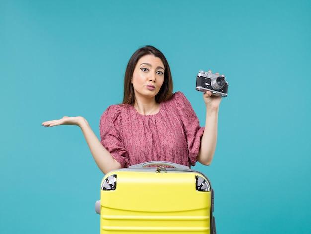 Vue de face jeune femme en vacances prenant photo avec appareil photo sur le fond bleu voyage mer voyage femme à l'étranger vacances