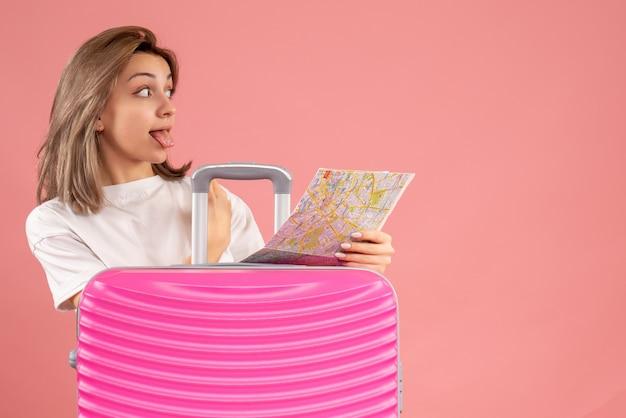 Vue de face jeune femme avec une valise rose qui sort la langue tenant la carte