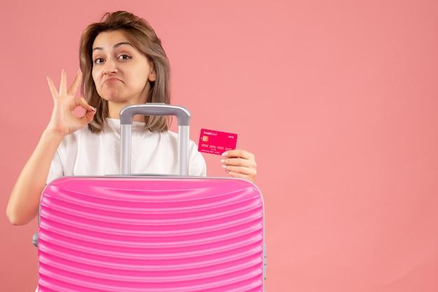 Vue de face jeune femme avec une valise rose tenant une carte faisant signe ok