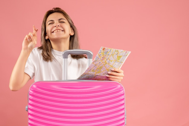 Vue de face jeune femme avec une valise rose tenant une carte faisant signe de souhait